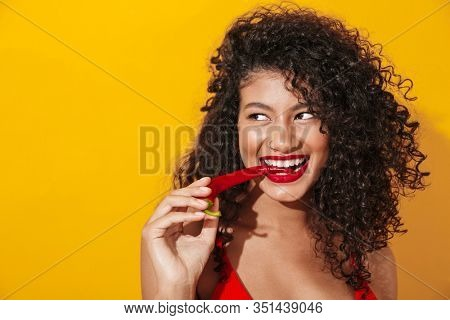 Image of beautiful brunette african american woman wearing swimsuit eating hot spicy chilly pepper isolated over yellow background