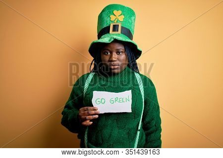 Plus size african american woman wearing green hat holding paper on saint patricks day with a confident expression on smart face thinking serious