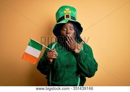 Plus size african american woman wearing green hat holding irish flag on saint patricks day cover mouth with hand shocked with shame for mistake, expression of fear, scared in silence, secret concept