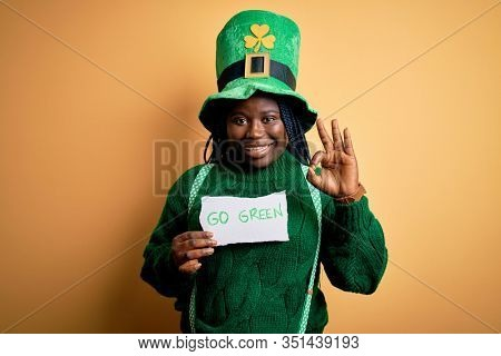 Plus size african american woman wearing green hat holding paper on saint patricks day doing ok sign with fingers, excellent symbol