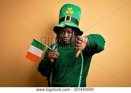 Plus size african american woman wearing green hat holding irish flag on saint patricks day with angry face, negative sign showing dislike with thumbs down, rejection concept