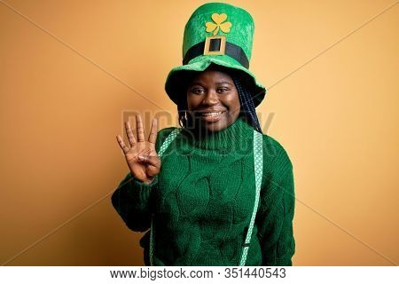 Plus size african american woman with braids wearing green hat with clover on st patricks day showing and pointing up with fingers number four while smiling confident and happy.