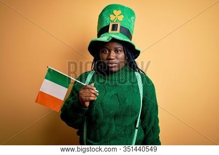 Plus size african american woman wearing green hat holding irish flag on saint patricks day with a confident expression on smart face thinking serious