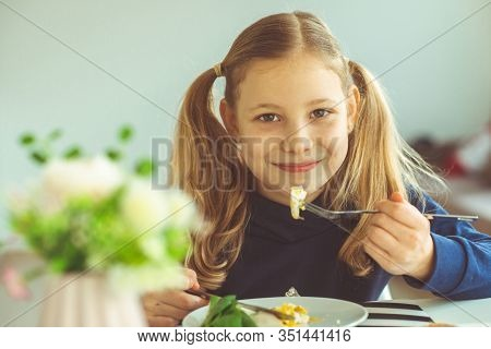 Cute Blonde Teen Girl Eating Eggs Benedict With Knife And Fork