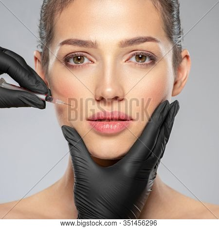 Young caucasian woman getting botox cosmetic injection near the eyes. Beautiful woman gets botox injection in her face. Adult girl gets cosmetic injection of botox in a clinic. Beauty treatments