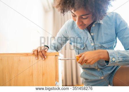 Afro Woman Repairing Furniture At Home.