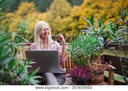 Senior Woman With Laptop Sitting Outdoors On Terrace, Working.