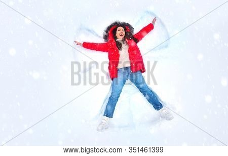 Snow Angel Concept. Happy Woman Enjoying First Snow, Lying In Snow And Making Snow Angel. Winter Hol