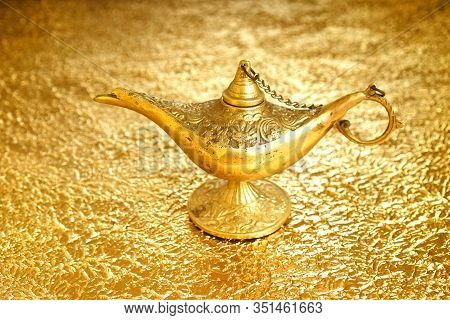 Lamp Of Wishes - Aladdin Lamp On A Golden Background. The Concept Of Wealth And Fulfillment Of Desir