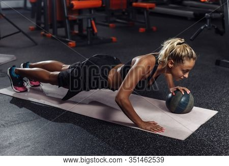Young Attractive Sport Woman In Sportswear Is Practicing Push-ups With A Medicine Ball In The Gym. F