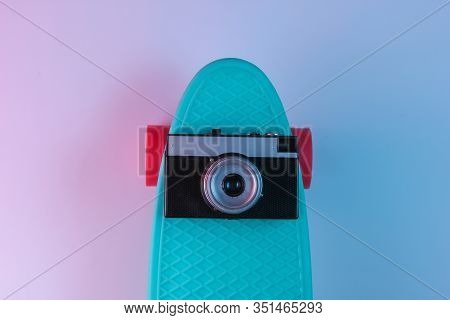 Plastic Mini Cruiser Board And Retro Camera On Background With Blue Pink Neon Gradient Ligh. Top Vie