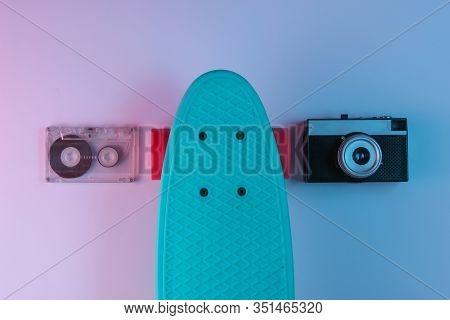 Plastic Mini Cruiser Board, Audio Tape, Retro Camera On Background With Blue Pink Neon Gradient Ligh
