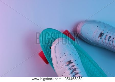 White Sneakers On Plastic Mini Cruiser Board With Blue Pink Neon Gradient Ligh. Top View