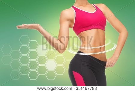 sport, fitness and diet concept - close up of slim fit woman's body with trained abs over green background