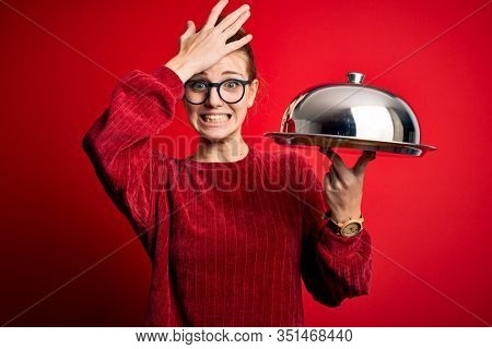 Young beautiful redhead woman holding waitress tray over isolated red background stressed with hand on head, shocked with shame and surprise face, angry and frustrated. Fear and upset for mistake.