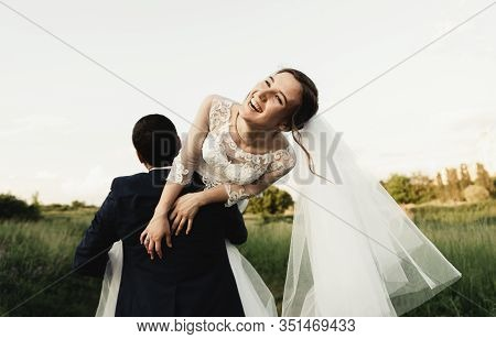 Happy Bridegroom Raises Bride In Summer Park. Man Raised And Hug Woman To Her Arms. Newly Wedded Cou