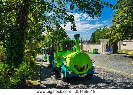 Tourist Train Near Nitra Castle In Old Town Of Nitra, Slovakia. Sightseeing Green Bus With Tourists