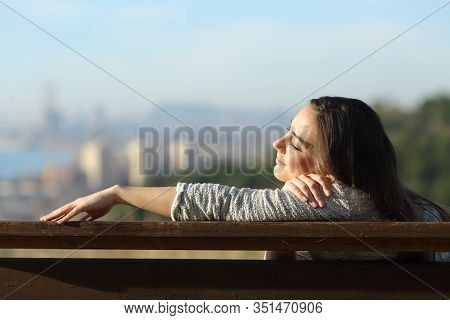 Relaxed Woman Resting Napping Sitting On A Bench In City Outtskirts
