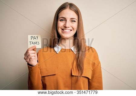 Young beautiful blonde woman holding pay taxes to goverment reminder over yellow background with a happy face standing and smiling with a confident smile showing teeth