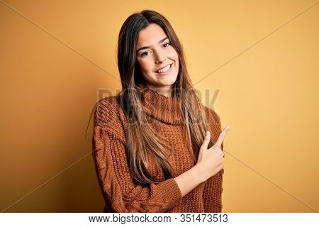Young beautiful girl wearing casual sweater standing over isolated yellow background cheerful with a smile of face pointing with hand and finger up to the side with happy and natural expression