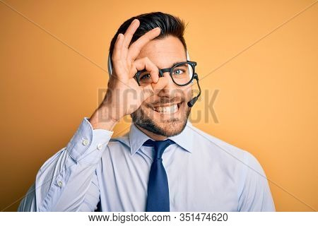 Young business operator man wearing customer service headset from call center doing ok gesture with hand smiling, eye looking through fingers with happy face.