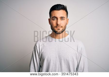 Young handsome man wearing casual t-shirt standing over isolated white background with serious expression on face. Simple and natural looking at the camera.