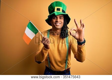 African american man wearing green hat holding irish ireland flag celebrating saint patricks day doing ok sign with fingers, excellent symbol