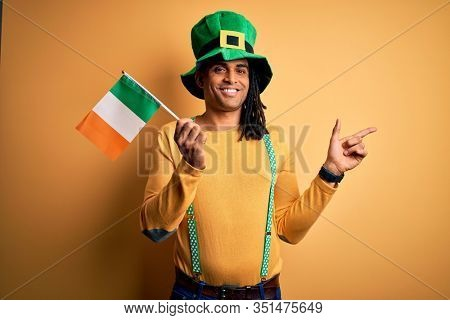 African american man wearing green hat holding irish ireland flag celebrating saint patricks day very happy pointing with hand and finger to the side