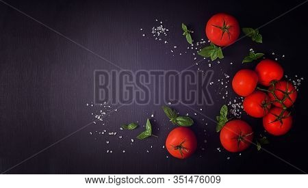 Italian Cooking Ingredients. Tomatoes And Basil On A Dark Wooden Table. Food Background For Tasty It
