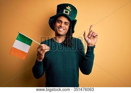 African american man wearing green hat holding irish ireland flag celebrating saint patricks day surprised with an idea or question pointing finger with happy face, number one