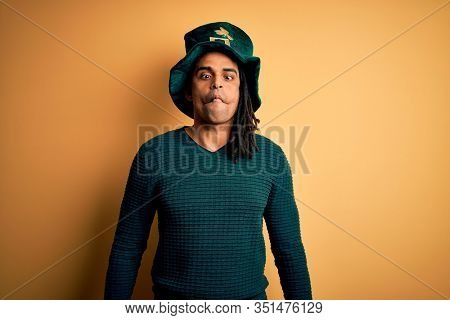 Young african american man wearing green hat with clover celebrating saint patricks day making fish face with lips, crazy and comical gesture. Funny expression.