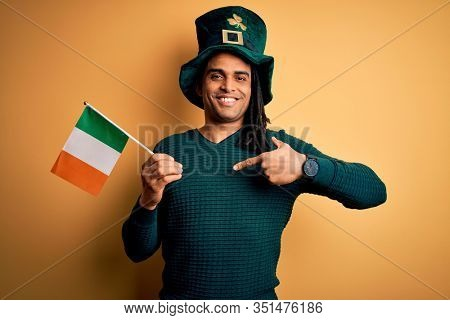 African american man wearing green hat holding irish ireland flag celebrating saint patricks day with surprise face pointing finger to himself