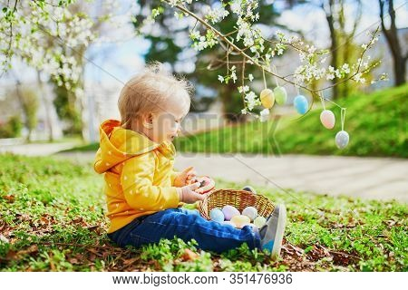 Cute Little One Year Old Girl Playing Egg Hunt On Easter. Toddler Sitting On The Grass Under Apple T