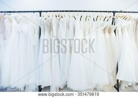 Horizontal no people shot of beautiful wedding dresses on clothes rails in modern bridal dress-making studio