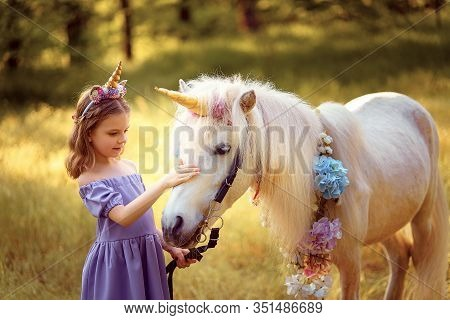 Girl In Purple Dress With Wreath Of A Unicorn In Hair Hugging And Kissing White Unicorn. Dreams Come