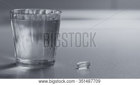 Full Glass Of Water And Vitamin E Capsule On The Table. Bw Photo.