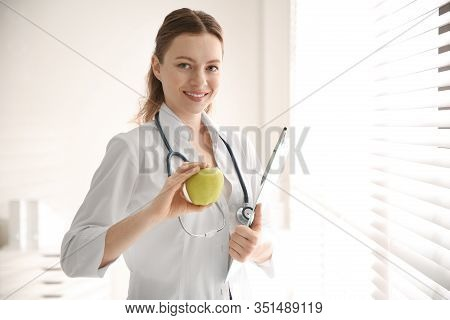 Nutritionist With Apple And Clipboard Near Window In Office. Space For Text