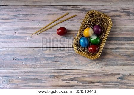The Easter Composition. Two Candles And A Varicoloured Eggs On Wooden Table Close-up.