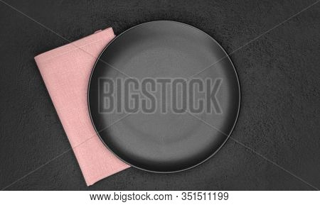 Black Plate With Flatware And Pink Napkin On Black Stone Table Top View. Table Setting.
