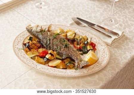 Grilled sea bass with vegetables on restaurant table, Mediterranean dish