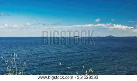 A Creative Imaginative Cerulean Sky With White Fluffy Clouds Over Water And An Island On The Horizon