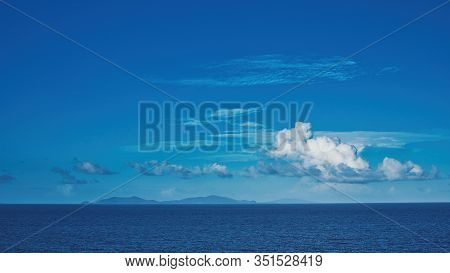 A Creative Imaginative Cerulean Sky With A White Fluffy Clouds Over Water And Islands On The Horizon
