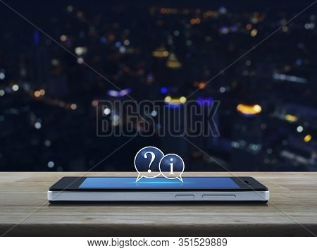 Question Mark And Information Chat Icon On Modern Smart Mobile Phone Screen On Wooden Table Over Blu