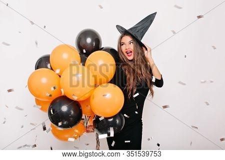 Good-humoured Woman With Red Lips Posing In Carnival Hat. Glamorous Girl With Orange Balloons Standi