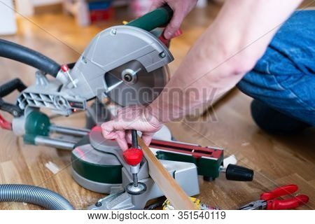 Carpenter At Work. Man Carpenter Cutting Wooden Plank With Circular Saw. Carpenter Working On Hardwo