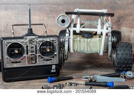 Radio-controlled Car Model With Scattered Tools For Repairing Rc Buggy Models And A Control Panel.