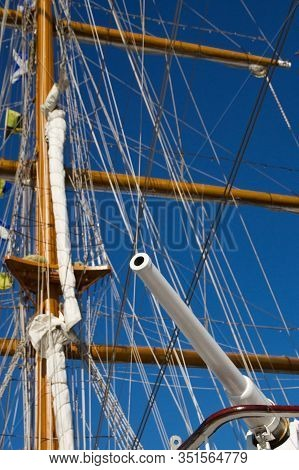 White Gun On Background Masts Of Parsing Ship Mast Sailing Ship Against The Blue Sky