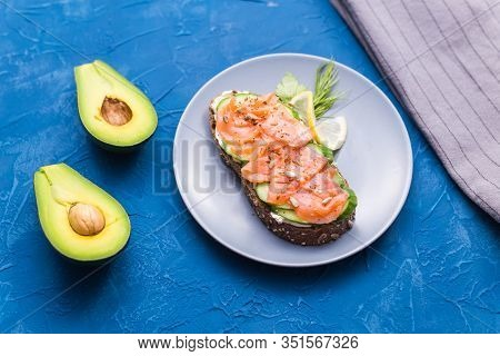 Sandwich With Smoked Salmon And Cucumber On Blue Background With Avocado, Top View. Concept For Heal