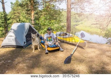 Ryazan, Russia - 06.09.2019: Man With Tatoo Sitting On Mat With Dog Near Camping Tent And Kayak.