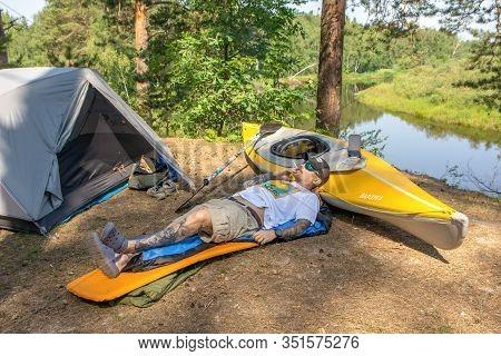 Ryazan, Russia - 06.09.2019: Man With Tatoo Lies On Camping Mat Near Tent And Kayak